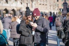 Μόναχο, Γερμανία 17 Φεβρουαρίου 2019 Όμορφο νέο ευτυχές ζεύγος που εξετάζει την επίδειξη smartphone στο κέντρο πόλεων στοκ φωτογραφία με δικαίωμα ελεύθερης χρήσης