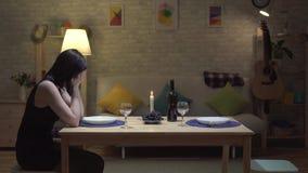 Μόνη χαριτωμένη συνεδρίαση brunette σε έναν πίνακα σε ένα σύγχρονο σπίτι με το φως ιστιοφόρου και να φωνάξει απόθεμα βίντεο