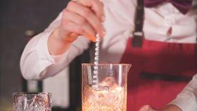 Μπάρμαν που αναμιγνύει τα συστατικά κοκτέιλ με ένα μακρύ κουτάλι στο υψηλό γυαλί απόθεμα βίντεο