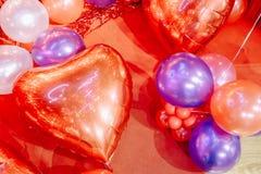 Μπαλόνια αέρα διαμορφωμένου του καρδιά φύλλου αλουμινίου στο κόκκινο υπόβαθρο κρητιδογραφιών άνδρας αγάπης φιλιών έννοιας στη γυν στοκ φωτογραφία με δικαίωμα ελεύθερης χρήσης
