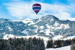 Μπαλόνι ζεστού αέρα πέρα από το χιονισμένο τοπίο στα προ-όρη, Βαυαρία, Γερμανία στοκ φωτογραφία