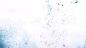 Μπλε ξηρά μελάνια που εμπίπτουν στο σαφές νερό και που χρωματίζουν το, πλάγια όψη Σκόνη χρωμάτων που αναμιγνύει με το σαφές νερό  απόθεμα βίντεο