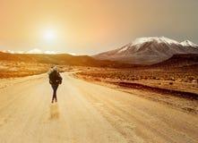 Νέα ανύπαντρη με τον περίπατο σακιδίων πλάτης στο βρώμικο δρόμο προς μια κορυφογραμμή βουνών Ύφος Backpackers στοκ εικόνες