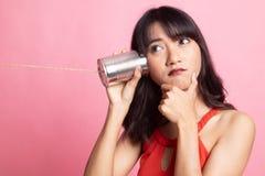 Νέα ασιατική ακρόαση γυναικών με το τηλέφωνο δοχείων κασσίτερου και σκέψη στοκ εικόνες