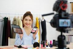 Νέα ασιατική ομορφιά γυναικών blogger που επιδεικνύει πώς να αποτελέσει την τηλεοπτική διδακτική καταγραφή από τη κάμερα, vlog έν στοκ φωτογραφίες