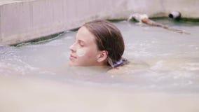 Νέα γυναίκα με τη μάσκα λάσπης στη χαλάρωση προσώπου δερμάτων στην ορυκτή λάσπη στην υπαίθρια SPA Όμορφη γυναίκα που κολυμπά στο  φιλμ μικρού μήκους