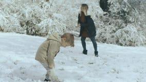 Νέα γυναίκα με το μακροχρόνιο παιχνίδι ξανθών μαλλιών με το γιο της το χειμώνα στο χιονώδες πάρκο 4k απόθεμα βίντεο