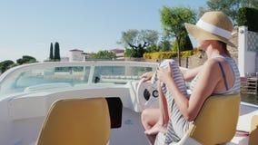 Νέα γυναίκα που απολαμβάνει διακοπές στο ευρωπαϊκό θέρετρο Επιπλέοντας σε μια βάρκα στο κανάλι Empuriabrava, Ισπανία φιλμ μικρού μήκους