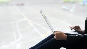 Νέα γυναίκα που εργάζεται στο lap-top στον αερολιμένα φιλμ μικρού μήκους