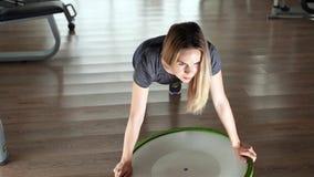 Νέα γυναίκα που κάνει την άσκηση στη σφαίρα bosu Τοπ όψη φιλμ μικρού μήκους