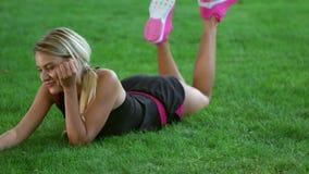 Νέα γυναίκα που κάνει την τηλεοπτική συνομιλία στο κινητό τηλέφωνο στο πάρκο Αθλήτρια φιλμ μικρού μήκους