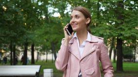 Νέα γυναίκα που μιλά στο τηλέφωνο στο πάρκο απόθεμα βίντεο