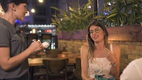 Νέα γυναίκα που διατάζει τα τρόφιμα στον πίνακα στο εστιατόριο βραδιού Σερβιτόρα που παίρνει τη διαταγή από την όμορφη γυναίκα στ απόθεμα βίντεο