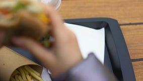 Νέα γυναίκα που τρώει το χάμπουργκερ, που έχει το μεσημεριανό γεύμα στο εστιατόριο γρήγορου φαγητού, απώλεια βάρους απόθεμα βίντεο