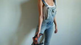 Νέα γυναίκα που φορά την ομοιόμορφη εργασία στο εργοτάξιο οικοδομής, που παίζει με το ηλεκτρικό τρυπάνι όπως ένα πυροβόλο όπλο φιλμ μικρού μήκους