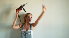 Νέα γυναίκα που φορά την ομοιόμορφη εργασία στο εργοτάξιο οικοδομής, που παίζει με το ηλεκτρικό τρυπάνι όπως ένα πυροβόλο όπλο απόθεμα βίντεο
