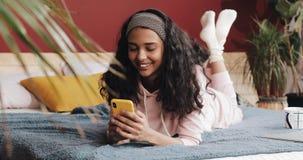 Νέα γυναίκα που χρησιμοποιεί το smartphone που βρίσκεται στο κρεβάτι στο πρωί κρεβατοκάμαρων απόθεμα βίντεο