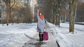Νέα ελκυστική γυναίκα στο θερμό παλτό και το ζωηρόχρωμο πλεκτό scaft περπάτημα τραβώντας τη μεγάλη ιώδη βαλίτσα της κατά τη διάρκ φιλμ μικρού μήκους