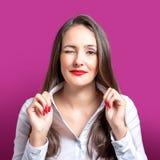 Νέα ευτυχής γυναίκα που κλείνει το μάτι στο φωτεινό υπόβαθρο στοκ φωτογραφία
