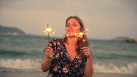 Νέα ευτυχής χαμογελώντας γυναίκα, που χορεύει μέσα με το sparkler στο ηλιοβασίλεμα σε σε αργή κίνηση, με τα πυροτεχνήματα στο ηλι φιλμ μικρού μήκους