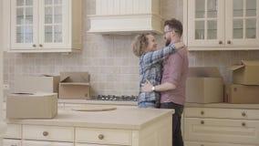 Νέα ευτυχή οικογενειακά φιλιά που στέκονται στην κουζίνα στο νέο διαμέρισμά τους Γενειοφόρος σύζυγος με τα γυαλιά σε ένα πουκάμισ φιλμ μικρού μήκους
