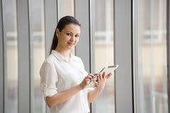 Νέα επιχειρηματίας που εργάζεται στο ipad υπερασπιμένος το παράθυρο στην αρχή Όμορφο νέο θηλυκό πρότυπο στην αρχή στοκ φωτογραφία