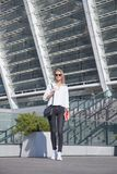 Νέα επιχειρησιακή γυναίκα στα γυαλιά ηλίου με την τσάντα στην πόλη που στέκεται με το σημειωματάριο στοκ εικόνες με δικαίωμα ελεύθερης χρήσης