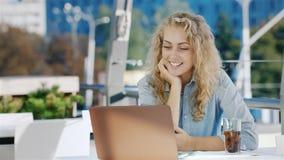 Νέα επιχειρησιακή γυναίκα που μιλά στην τηλεοπτική σύσκεψη ή την τηλεοπτική συνομιλία Χρησιμοποιώντας ένα lap-top, που κάθεται στ απόθεμα βίντεο