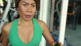 Νέα κατάλληλη και αθλητική ασιατική ταϊλανδική γυναίκα με το κατάλληλο τρέξιμο σωμάτων treadmill γυμναστικής που ιδρώνει εκπαιδευ απόθεμα βίντεο
