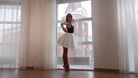 Νέα κατάρτιση ballerina γυναικών στο στούντιο που υπερασπίζεται το παράθυρο απόθεμα βίντεο