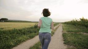 Νέα καυκάσια γυναίκα που απολαμβάνει τη ζωή και που τρέχει στον ισπανικό δρόμο επαρχίας μέσω του αγροτικού τοπίου τομέων σίτου φιλμ μικρού μήκους