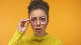 Νέα μαύρη γυναίκα που φαίνεται πιό στενή στον καθρέφτη, που παρατηρεί τις πρώτες ρυτίδες, φροντίδα δέρματος φιλμ μικρού μήκους