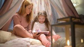 Νέα μητέρα και η κόρη της που έχουν τη διασκέδαση που χρησιμοποιεί την ταμπλέτα που παίζει apps φιλμ μικρού μήκους