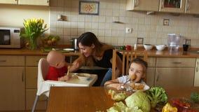 Νέα μητέρα που ταΐζει δύο παιδιά, που τρώνε τα φρούτα και το γαλακτοκομείο Υγιής διατροφή για τα παιδιά Γονέας με το παιδί και το απόθεμα βίντεο