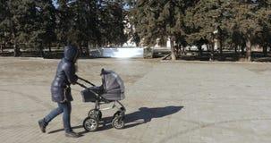 Νέα μητέρα που περπατά με έναν περιπατητή φιλμ μικρού μήκους