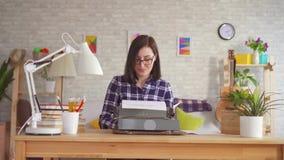 Νέα δακτυλογράφηση γυναικών με την έμπνευση σε μια γραφομηχανή απόθεμα βίντεο