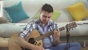 Νέα δημιουργική κιθάρα παιχνιδιού μουσικών ατόμων πορτρέτου και γράψιμο ενός τραγουδιού απόθεμα βίντεο