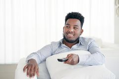 Νέα όμορφη και ελκυστική τηλεόραση προσοχής καναπέδων καναπέδων συνεδρίασης ατόμων μαύρων Αφρικανών αμερικανική στο σπίτι που χρη στοκ εικόνες