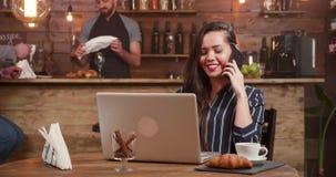 Νέα όμορφη κυρία που μιλά στο τηλέφωνό της εργαζόμενη στο lap-top της μακρινά απόθεμα βίντεο