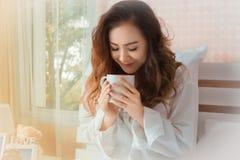 Νέα όμορφη μυρωδιά γυναικών των κουπών καφέ στην κρεβατοκάμαρα στοκ εικόνα με δικαίωμα ελεύθερης χρήσης