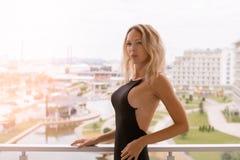 Νέα όμορφη ξανθή γυναίκα μόδας που φορά το μαύρο φόρεμα με την ανοικτή πλάτη στοκ φωτογραφία με δικαίωμα ελεύθερης χρήσης