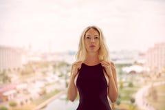 Νέα όμορφη ξανθή γυναίκα μόδας που φορά το μαύρο φόρεμα με την ανοικτή πλάτη στοκ φωτογραφίες