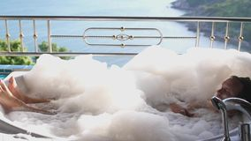 Νέα όμορφη χαλάρωση ατόμων σε ένα bathrtub με τον αφρό στο τροπικό θέρετρο με την καταπληκτική άποψη θάλασσας κίνηση αργή 3840x21 απόθεμα βίντεο