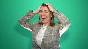 Νέα συγκλονισμένη έκπληκτη στάση γυναικών που απομονώνεται πέρα από το πράσινο υπόβαθρο κάμερα απόθεμα βίντεο
