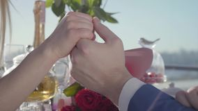 Νέα συνεδρίαση ζευγών που κρατά μαζί τα χέρια στον πίνακα εστιατορίων με την ανθοδέσμη των τριαντάφυλλων, σαμπάνια, καραμέλες απόθεμα βίντεο