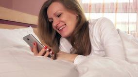 Νέα χαμογελώντας γυναίκα που κουβεντιάζει on-line με το smartphone φιλμ μικρού μήκους