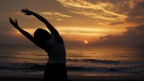 Νέα υγιής γιόγκα άσκησης γυναικών στην παραλία στα ωκεάνια κύματα ηλιοβασιλέματος Ισχυρή γυναίκα εμπιστοσύνης κάτω από το ηλιοβασ φιλμ μικρού μήκους