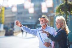 Νέα πόλη παρουσίας Το πλήρες μήκος του αισιόδοξου ηληκιωμένου και η γυναίκα στέκονται κοντά στο δρόμο και προσπαθούν να πιάσουν τ στοκ φωτογραφία με δικαίωμα ελεύθερης χρήσης