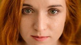 Νέα redhead γυναίκα με τις φακίδες που εξετάζει τη κάμερα στοκ φωτογραφία