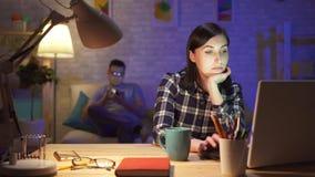 Νέες δεσποινίδες γυναικών που κάθονται σε ένα lap-top τη νύχτα σε ένα σύγχρονο διαμέρισμα απόθεμα βίντεο